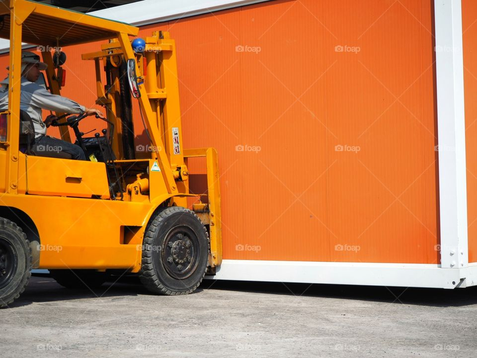 Forklift driver maneuvering while lifting an orange container.