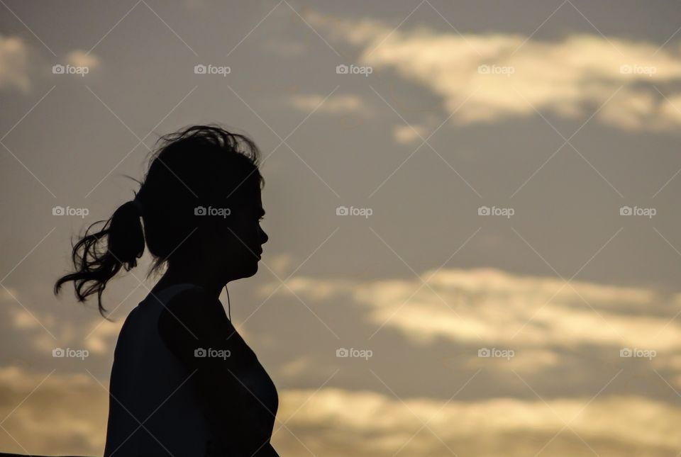 Silhouette of woman against sky at sunset