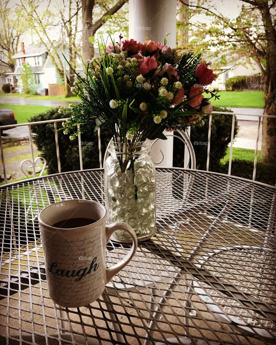 Coffee on the front porch, and flowers on table