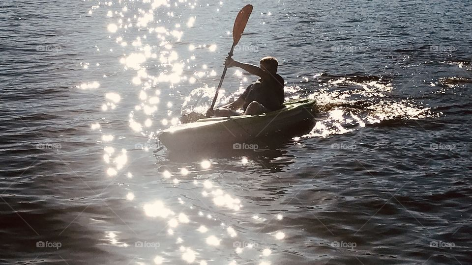 Gorgeous reflection of light on lake while boy is canoeing makes for a beautiful photo showing water's beauty!