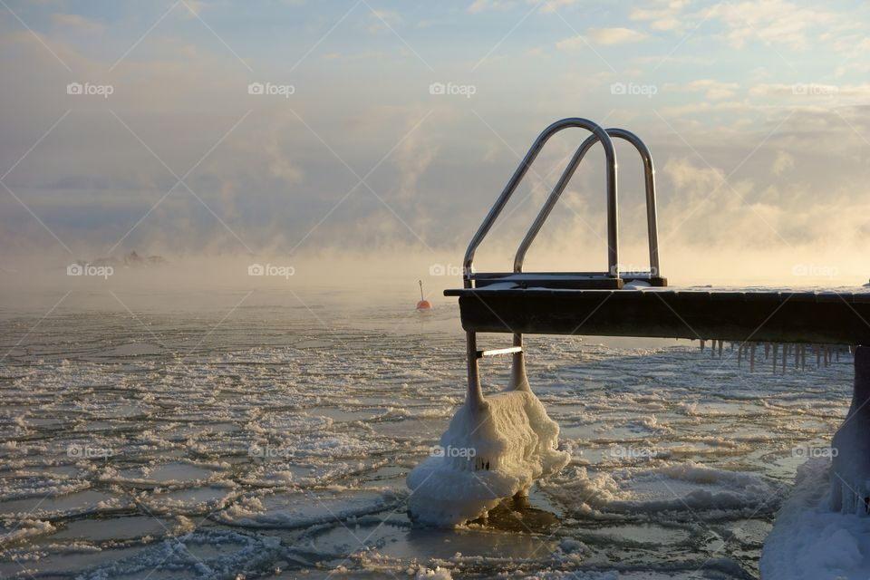 Ice covered swimming jetty and buoy in the freezing Baltic Sea in Helsinki, Finland