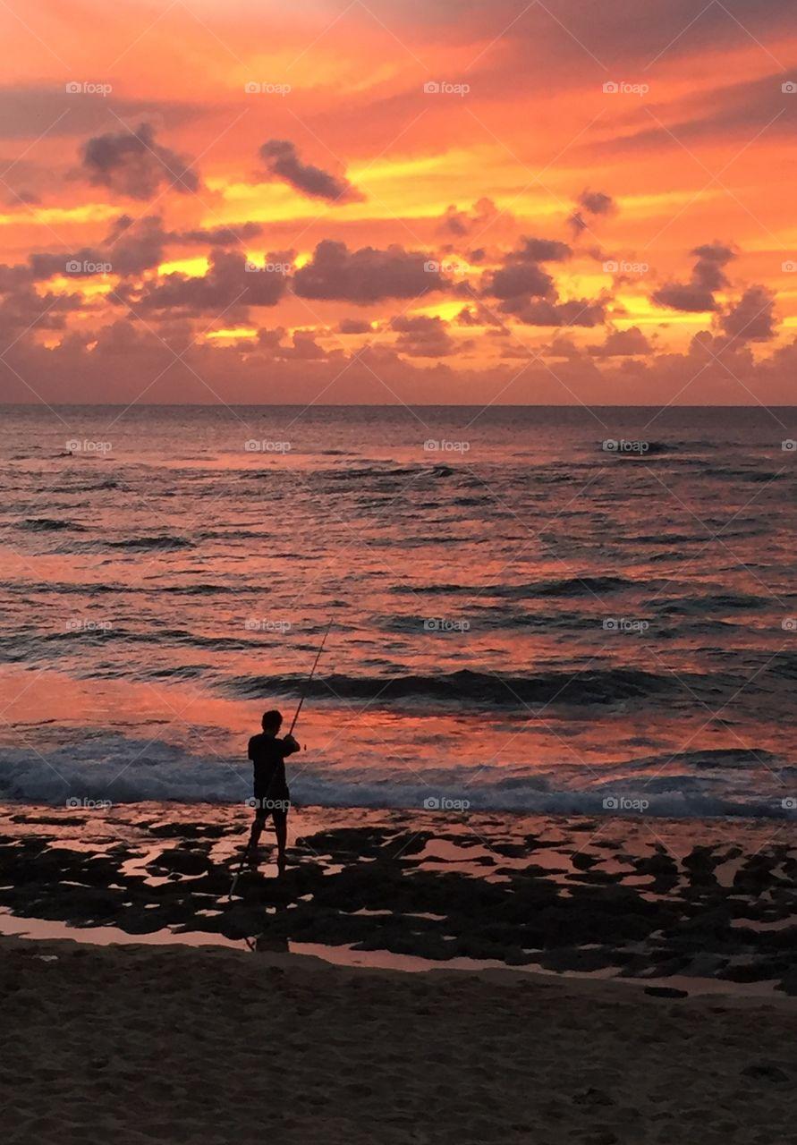 Fisherman at sunset at Laniakea Beach, Oahu, Hawaii