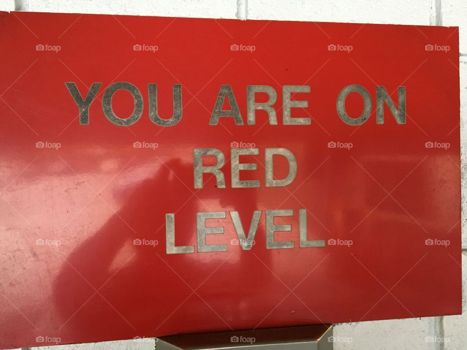 You are on red level sign with photographer reflection