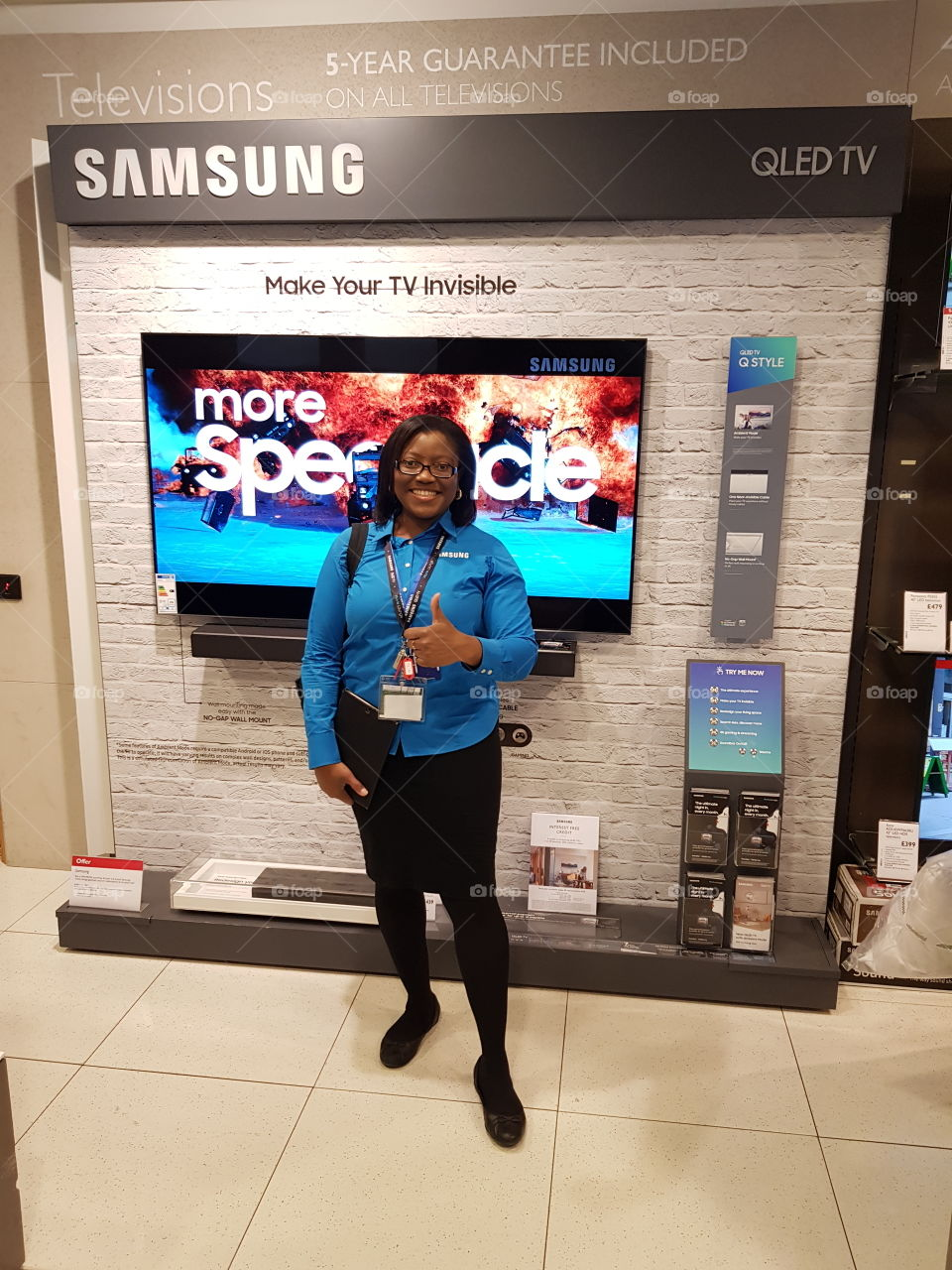 Samsung field force posing in front of QLED television display wall