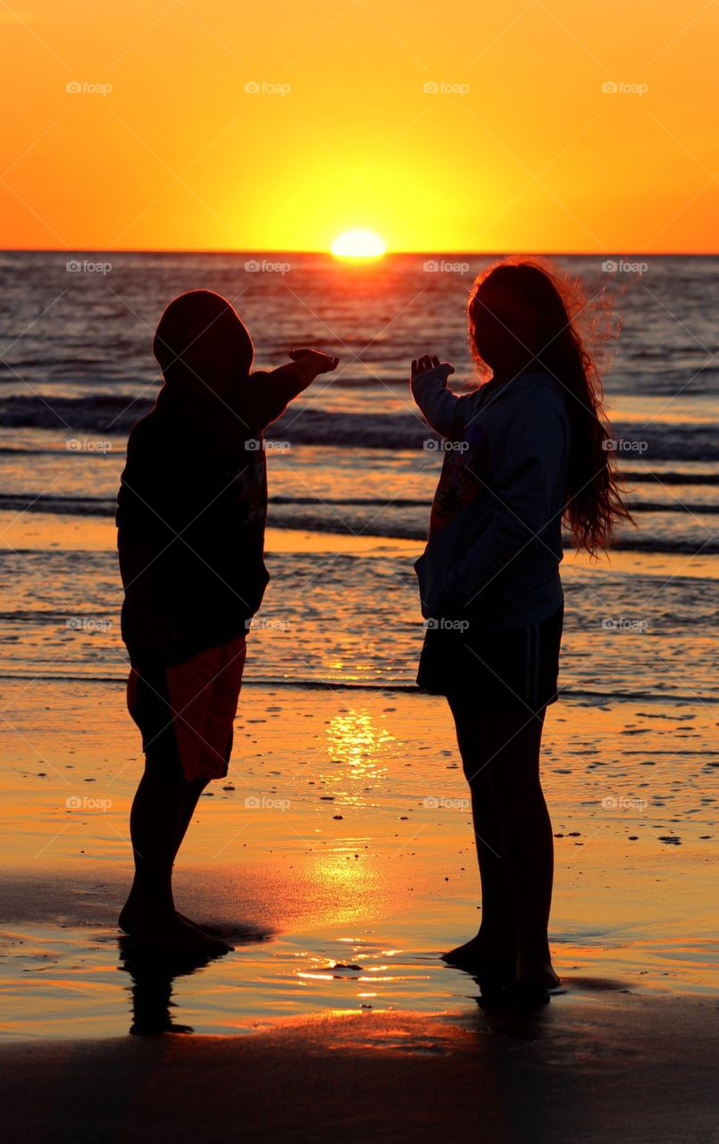 Silhouette of couple at beach during sunset with gesture
