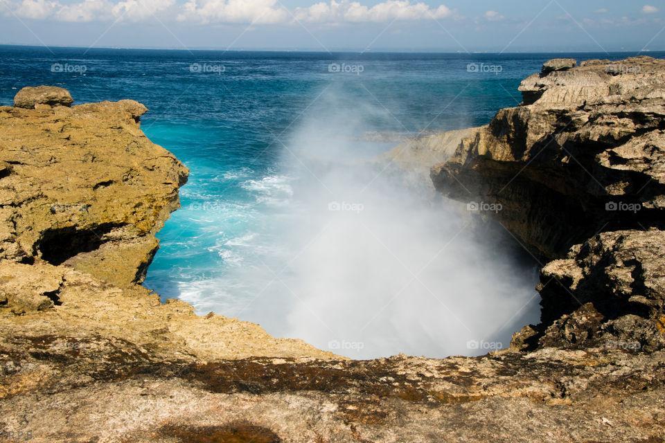 Waves crashing against the rocky shoreline of southern Nusa Lembongan Indonesia