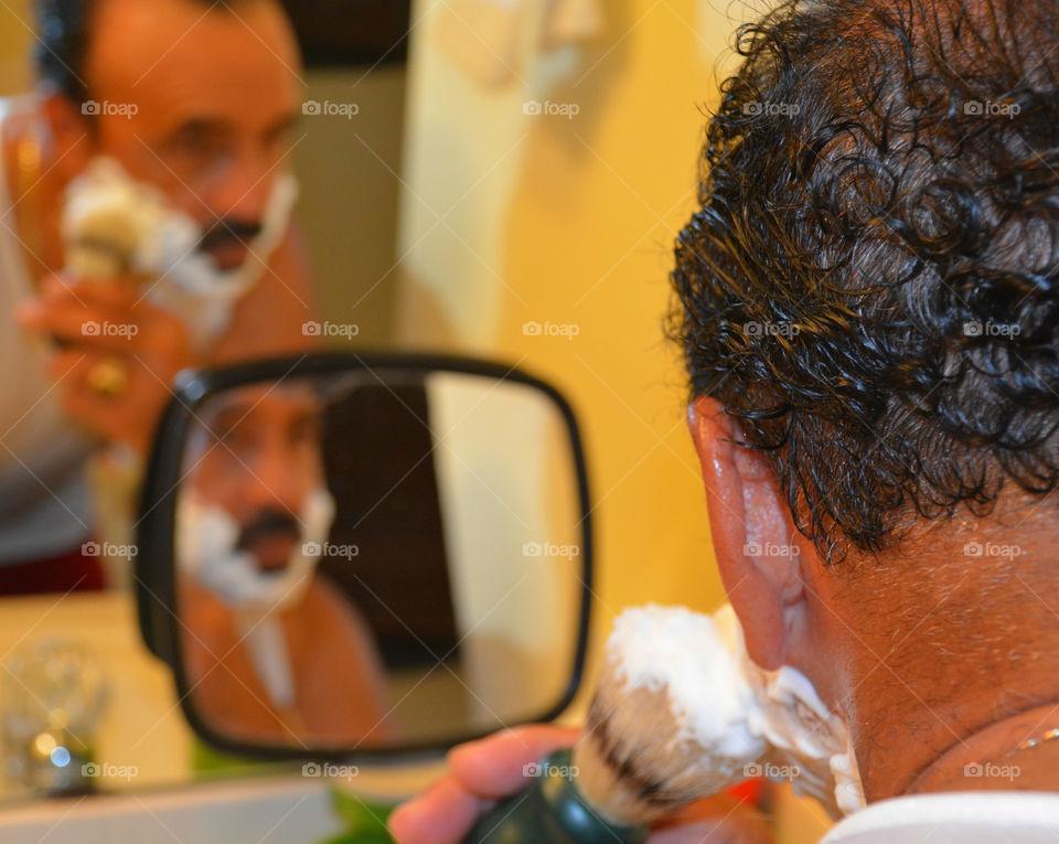 Portrait of a mature man shaving his beard