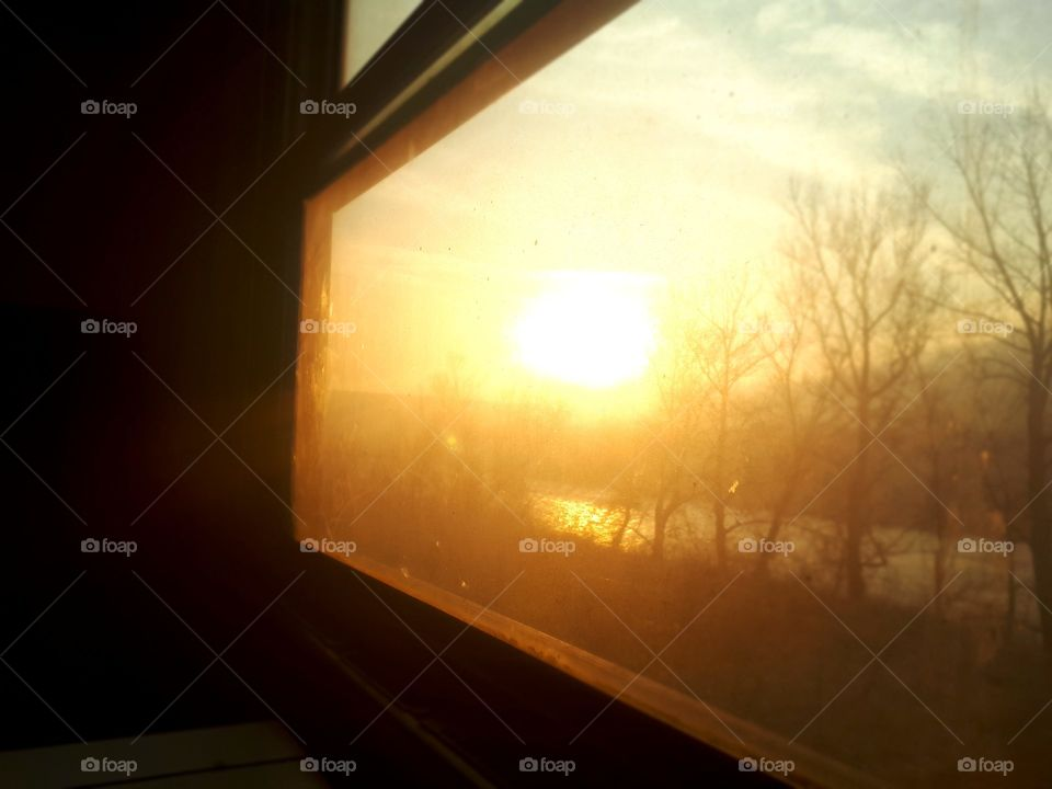 a view of the sunset through the window of the old passenger wagon