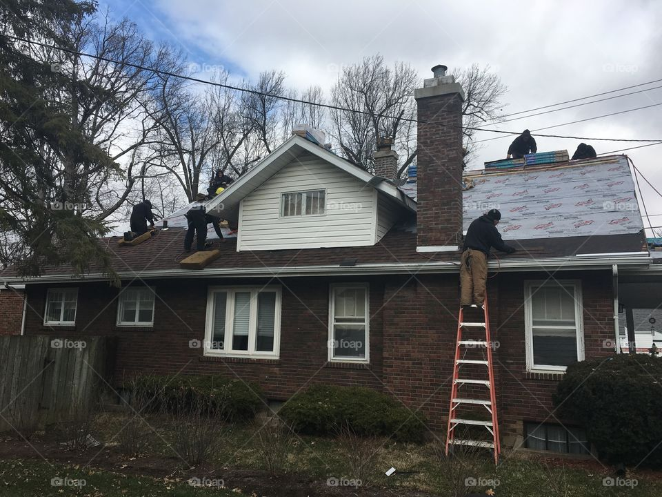 Men working on replacing the roof of our brick house with ladders and tools