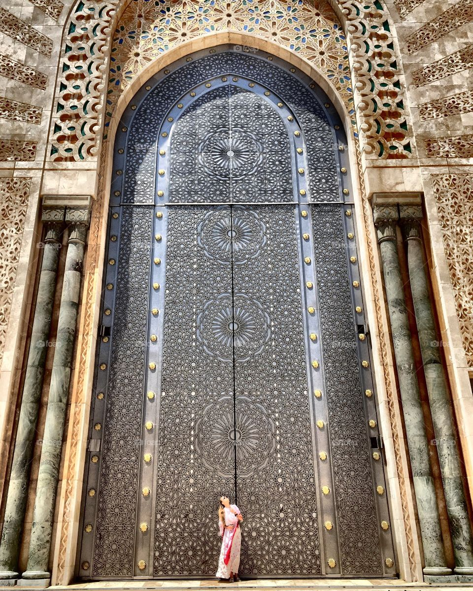 Woman standing at gate of hassan li mosque, Morocco