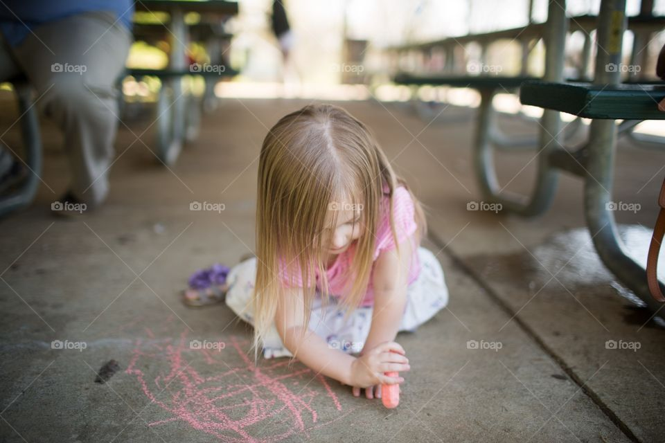 Girl drawing on concrete by picnic tables with sidewalk chalk. Young girl drawing on ground, creating pictures with chalk