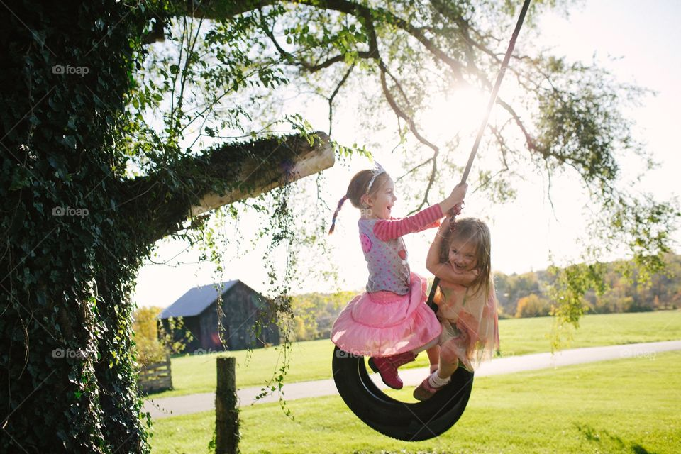 Young girls on tire swing in summertime. Laughing girls swinging on tire from a tree  in the summer