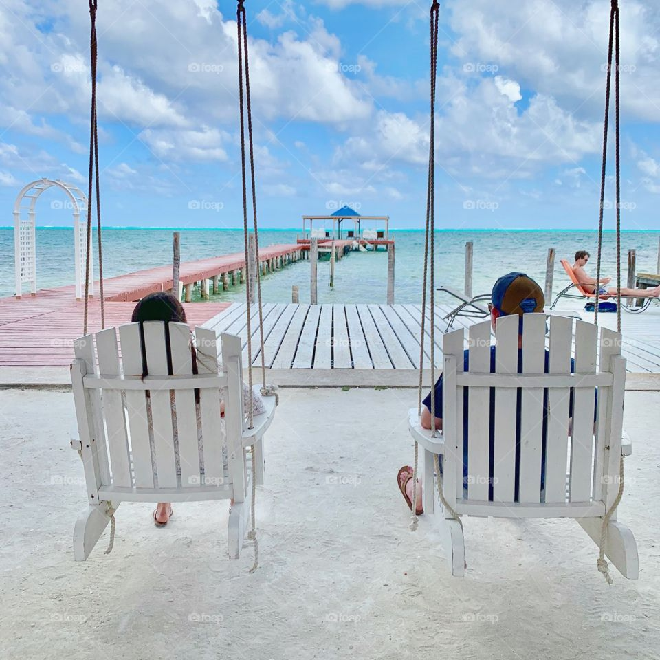 Two friends sitting in white chairs in the warm sun overlooking crystal blue waters in the Caribbean