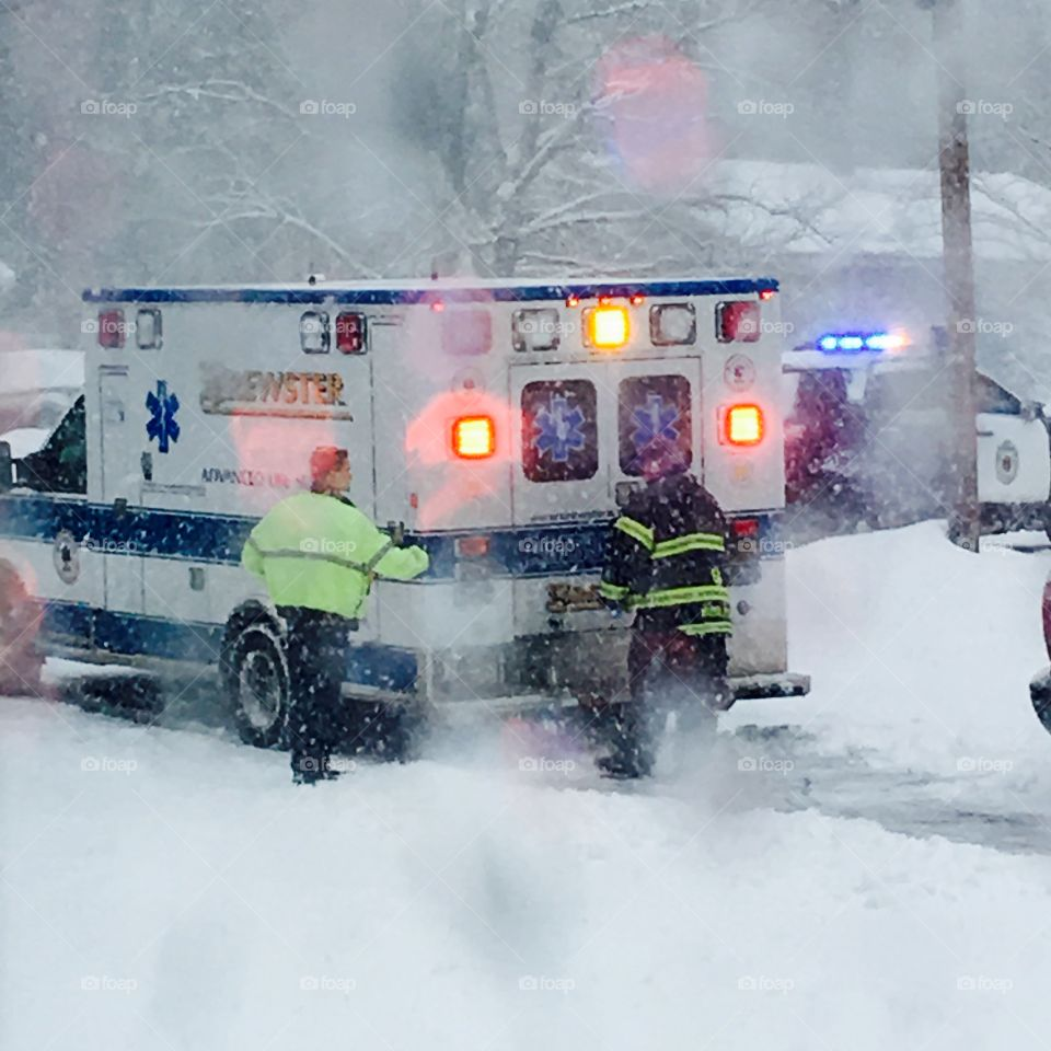 Ambulance in driveway w person inside on way to hospital while blizzard happening  Fireman & policeman are closing doors of ambulance as the sirens sound; lights flash and traffic is being stopped. The patient is in a medical situation on way to hospital!