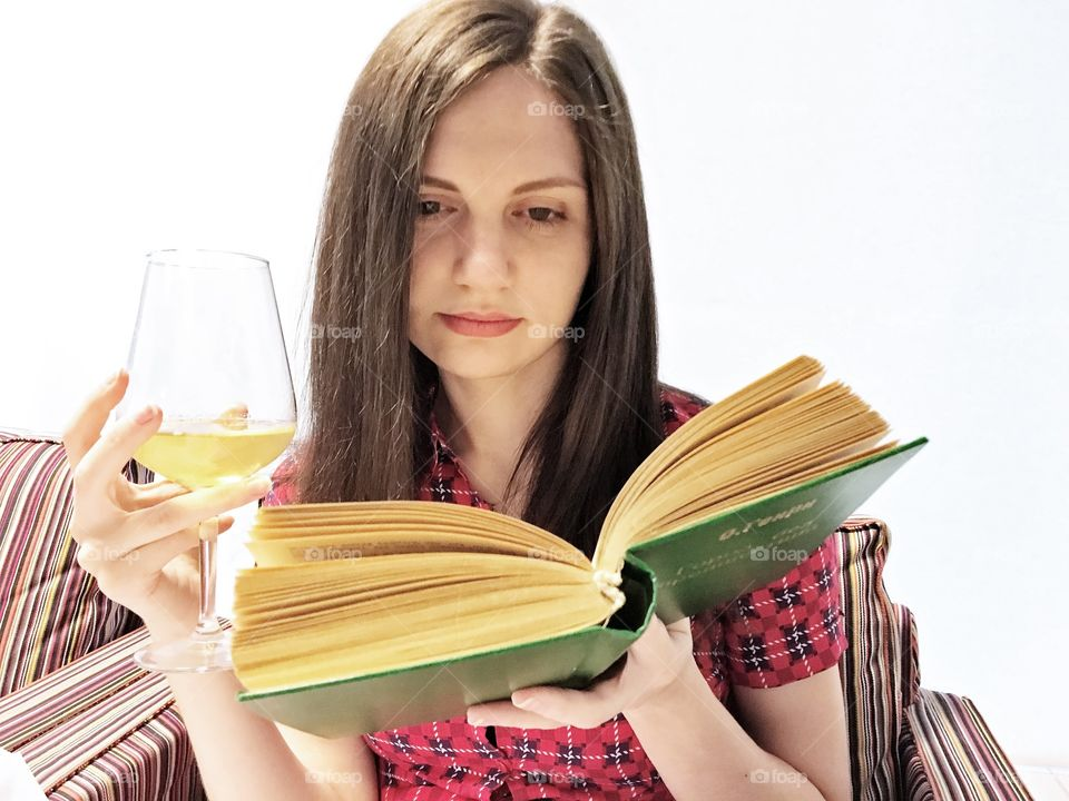 Young woman reading book with glass of drink in hand