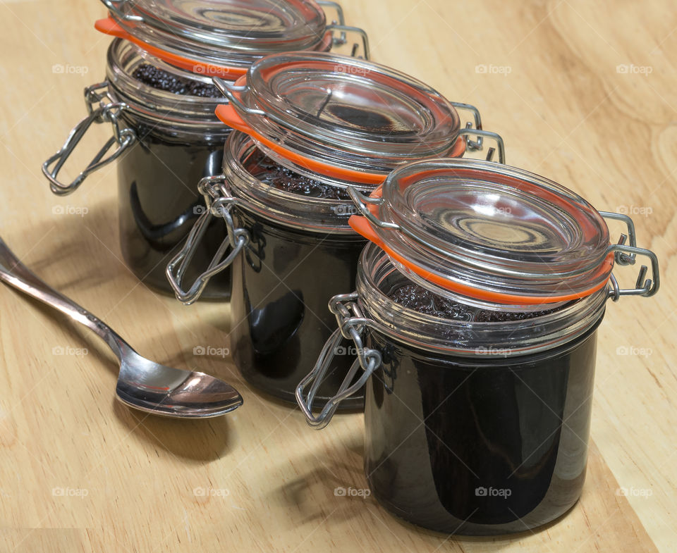 Lids ajar on three glass jars of mulberries in syrup on a wooden background.