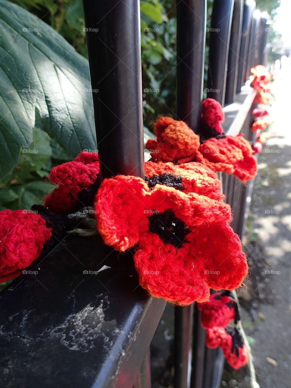 Rowe's of beautiful hand crocheted poppies of red and black along a dance in remembrance.