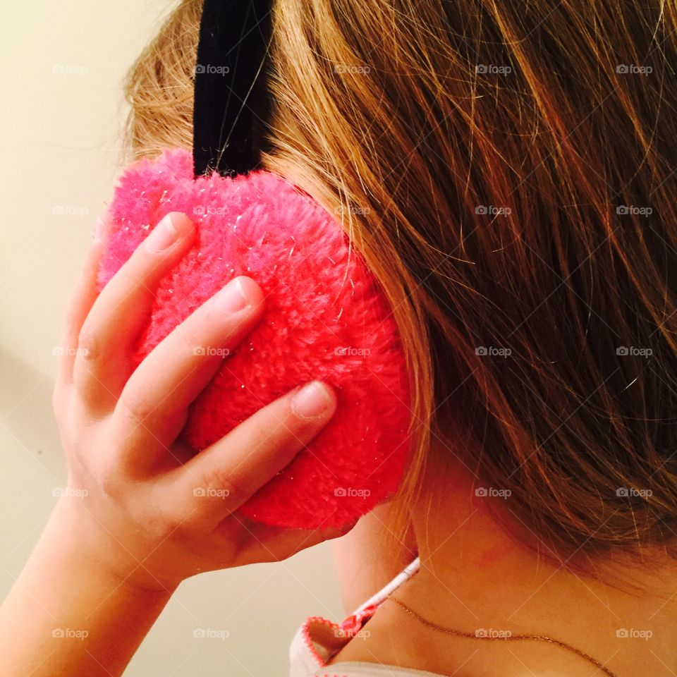 Close-up of a girl holding pink ear muff