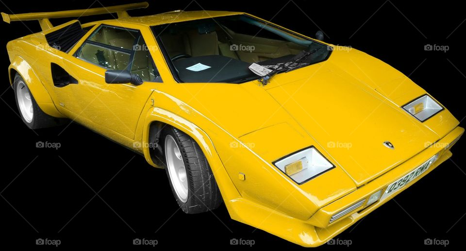 """ISOLATED on BLACK,    Yellow Lamborghini Countach   is a mid-engined, V12 sports car produced by Italian car manufacturer Lamborghini from 1974 to 1990. Its design pioneered and popularized the wedge-shaped, sharply angled look popular in many high-performance sports cars. It also popularized the """"cab forward"""" design concept, which pushes the passenger compartment forward to accommodate a larger engine.  In 2004, American car magazine Sports Car International named the car number three on the list of Top Sports Cars of the 1970s, and listed it number ten on their list of Top Sports Cars of the 1980s.  The rear wheels were driven by a traditional Lamborghini V12 engine mounted longitudinally with a mid-engined configuration. This contrasted with the Miura with its centrally mounted, transversely-installed engine. For better weight distribution, the engine is pointed """"backwards""""; the output shaft is at the front, and the gearbox is in front of the engine, the driveshaft running back through the engine's sump to a differential at the rear. Although originally planned as a 5 L (310 cu in) powerplant, the first production cars used the Lamborghini Miura's 4-liter engine. Later advances increased the displacement to 4754 cc and then (in the """"Quattrovalvole"""" model) 5167 cc with four valves per cylinder.  All Lamborghini Countaches were equipped with six Weber carburetors until the arrival of the 5000QV model, at which time the car became available in America, and used Bosch K-Jetronic fuel injection. The European models, however, continued to use the carburetors (producing more power than fuel-injected cars) until the arrival of the Lamborghini Diablo, which replaced the Countach."""