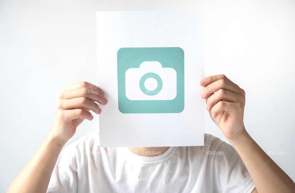 Young man holding a Foap logo in front of his face