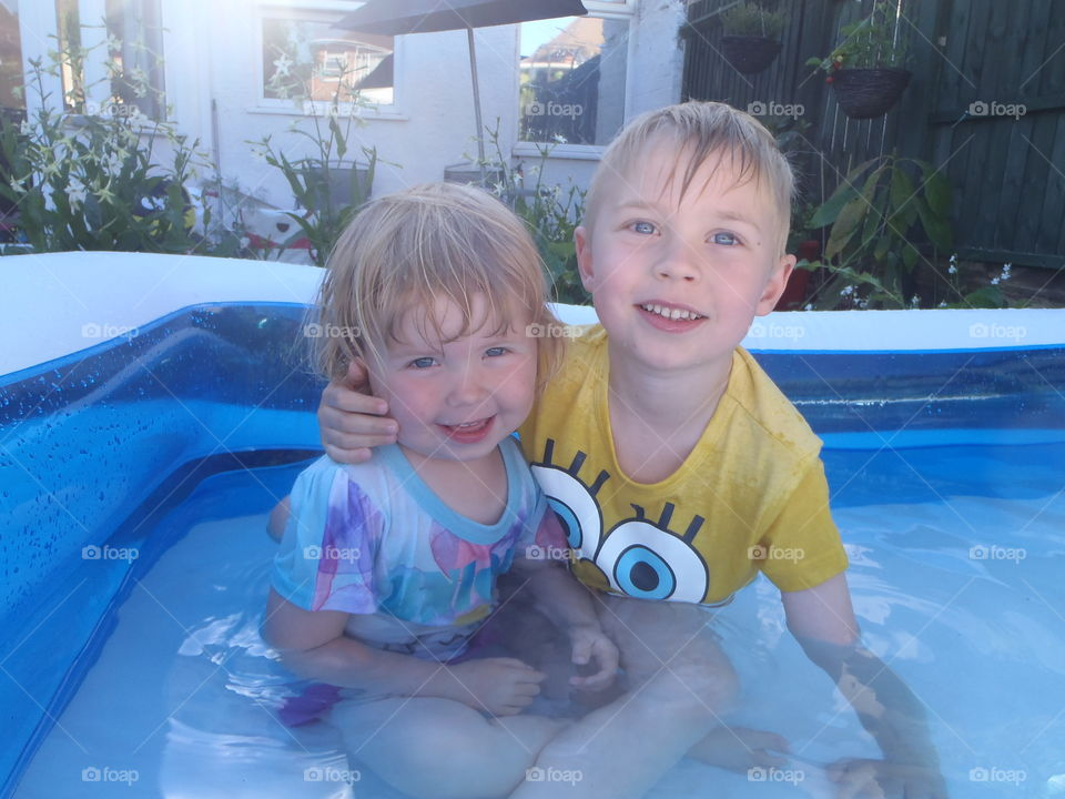 Two siblings sitting inside the inflatable tub