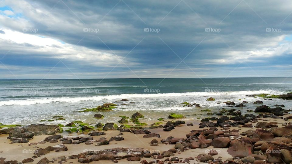Beautiful rock on the edge of the beach in the city of Torres in the state of Santa Catarina, Brazil. Rocky formation at the edge of the sea left beautiful photography.