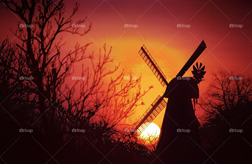 An English windmill silhouetted against the setting winter sun.