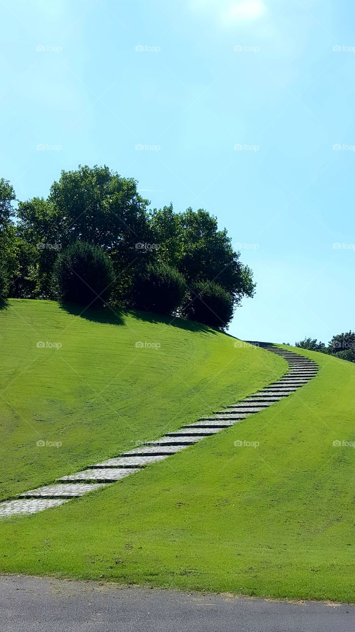 Stairs on green grass over the hill