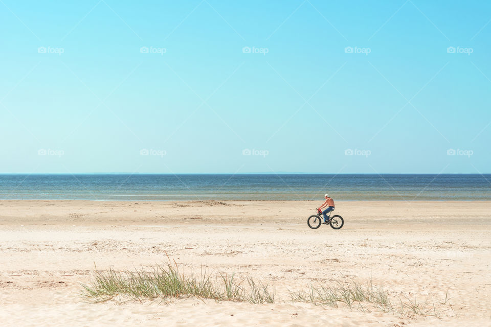 man is riding a bicycle along the beach
