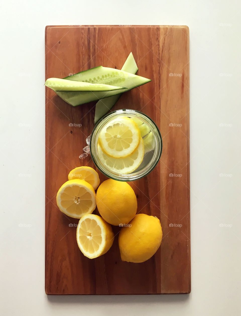 Fresh lemon/cucumber water. Cucumbers and lemons are on the cutting board for processing. Glass is like a ice and mark of cold refreshing water.