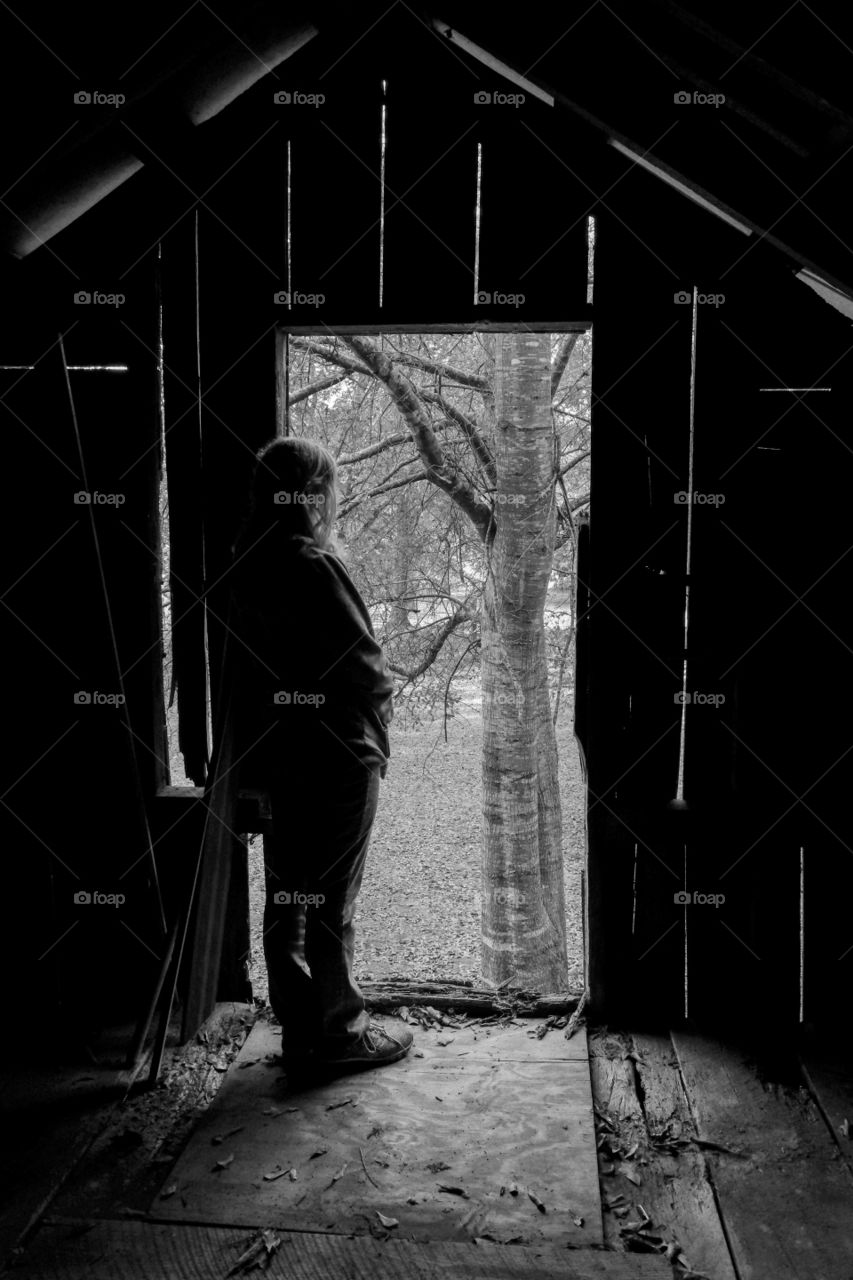 A young girl gazes out of the loft door of an old barn.