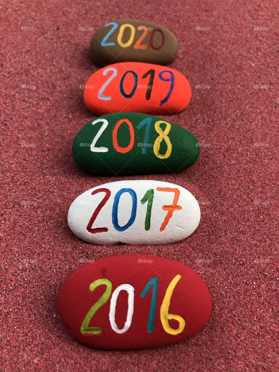 2016,2017,2018,2019,2020 on painted stones over red sand