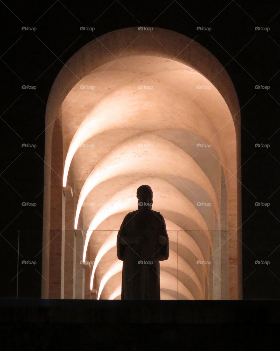 statue silhouette under a series of arches