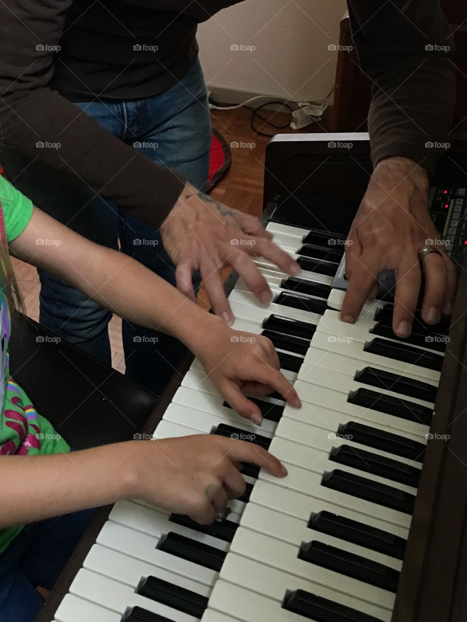 Father and daughter hands playing the organ together.