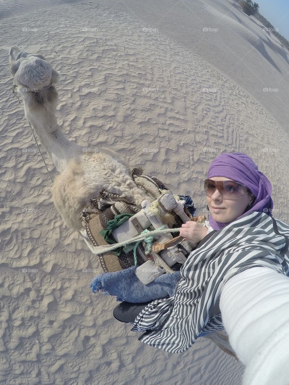 Girl riding a camel in the Sahara desert and taking a selfie
