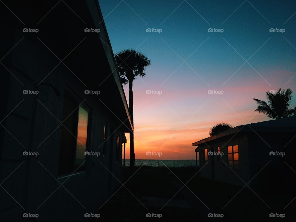 Classic old Florida beach houses at sunset with palm trees in background. Florida vacation homes with a beautiful sunset in background