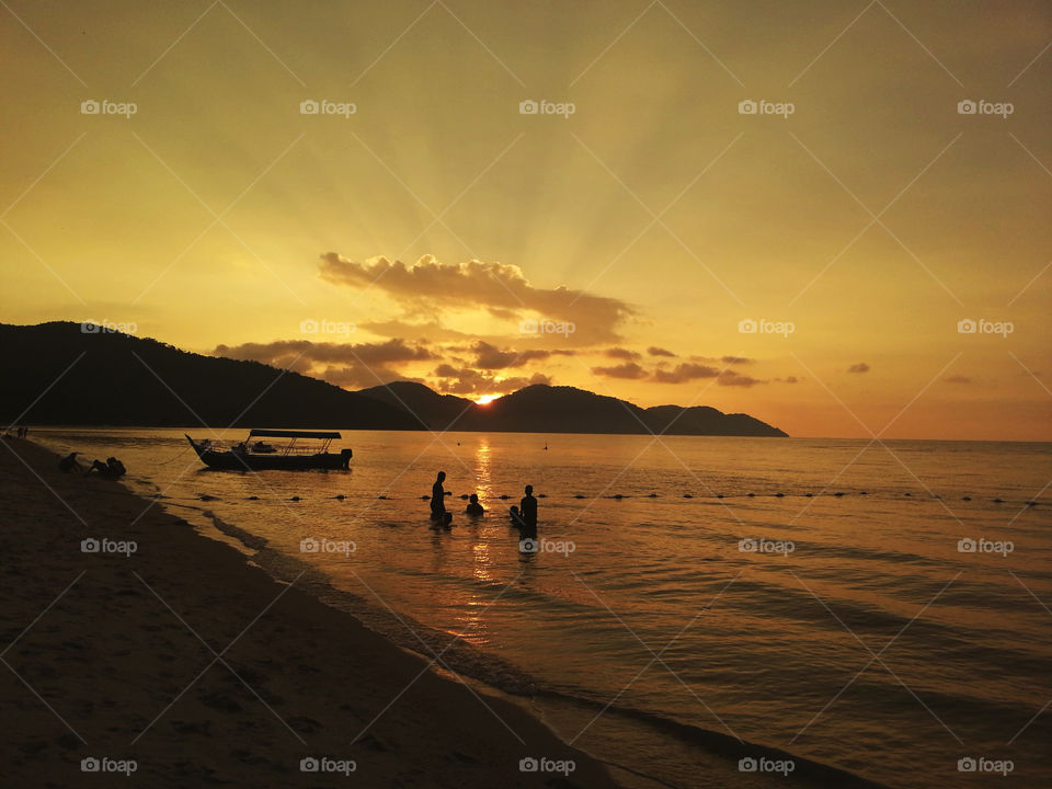 Silhouette of people enjoying themselves in Penang Beach,  Malaysia before the sun goes down