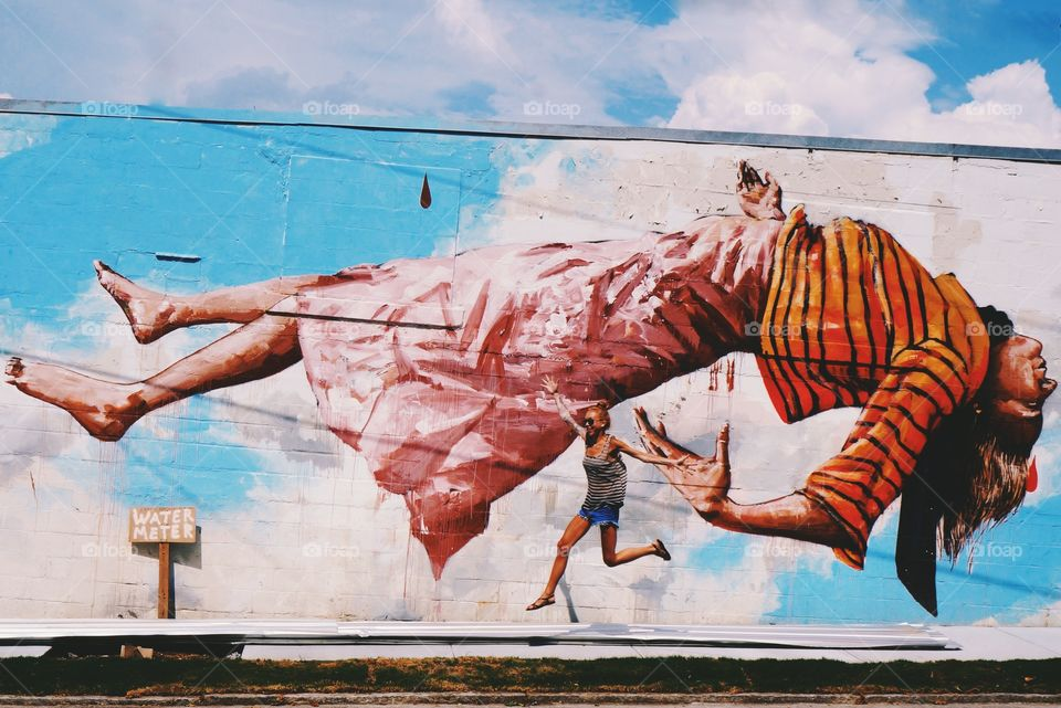Woman jumping in front of painted wall