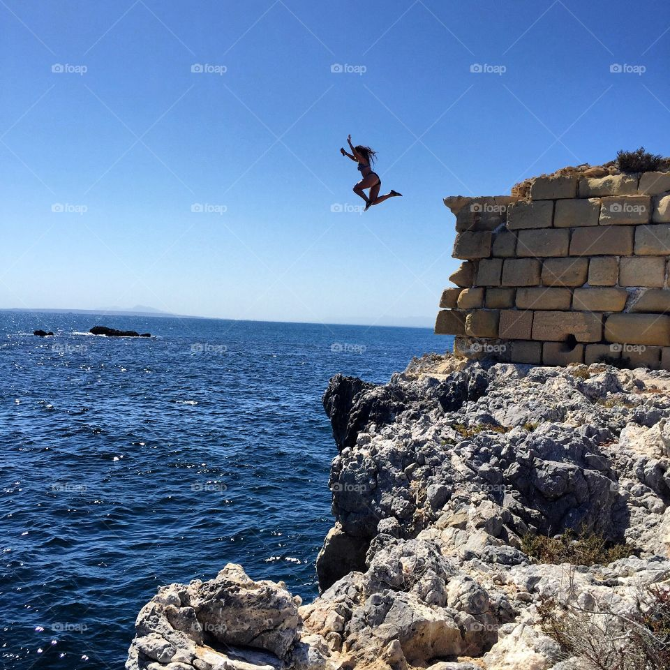 Woman jumping from cliff