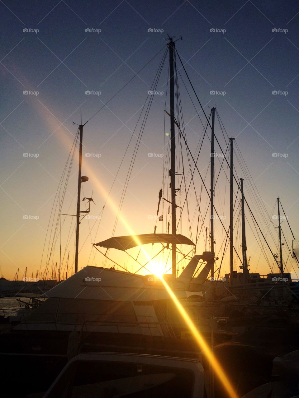 sun rays from behind the boats. boats at sunset with rays from behind the shadows