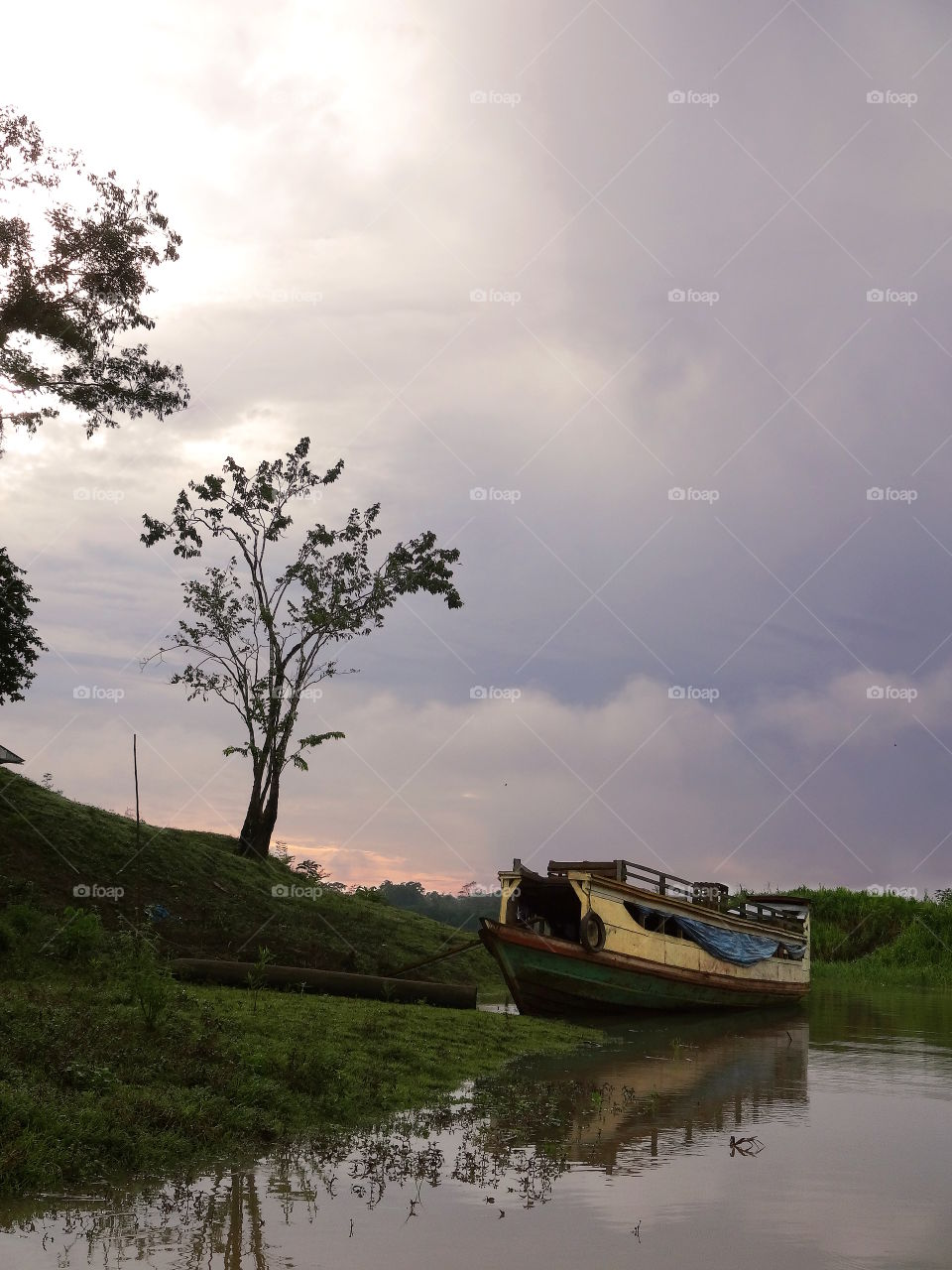 Decrepit house boat, amazon rainforest, 30 miles from Iquitos Peru. Purple stormy foreboding sky with orange sunset. Gloomy scene.