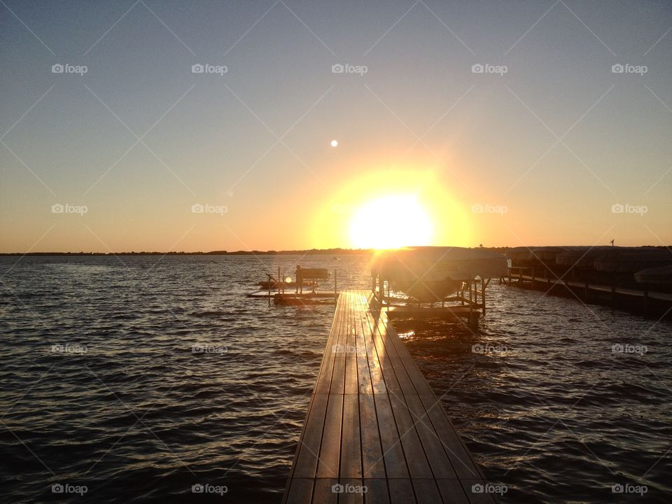 Gorgeous golden bright yellow sun is setting off in the distant horizon behind wooden dock!