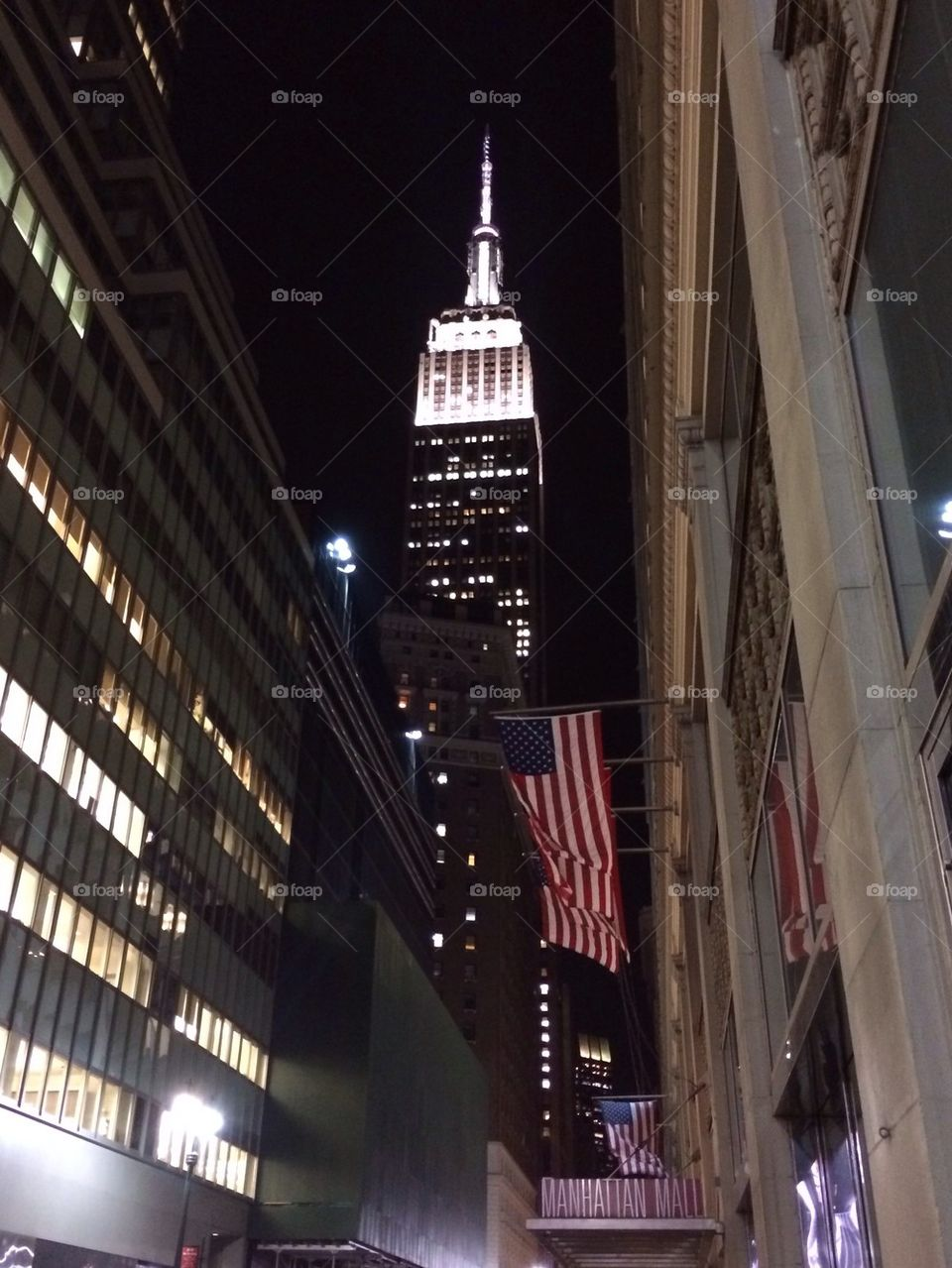 Empire State and American flags at night