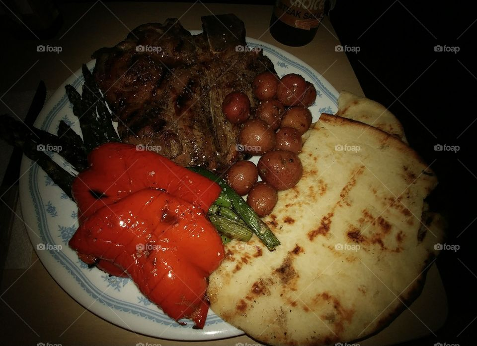 Grilled t-bone steak, grilled asparagus & sweet red peppers, rosemary roasted new potatoes, and grilled flat bread for dinner