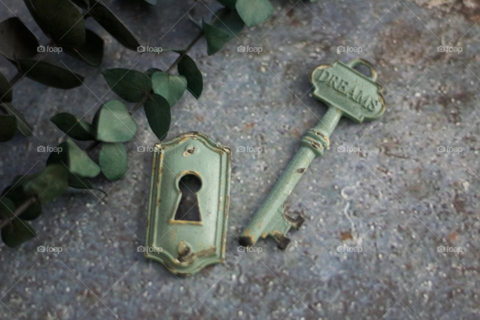 "Light teal, metal vintage key with embossed word, ""Dreams,"" and keyhole on concrete surface"