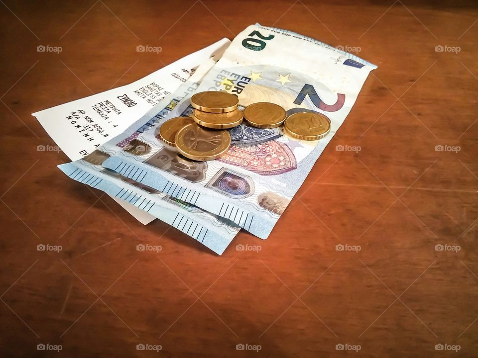 Euro note and coins on wooden table