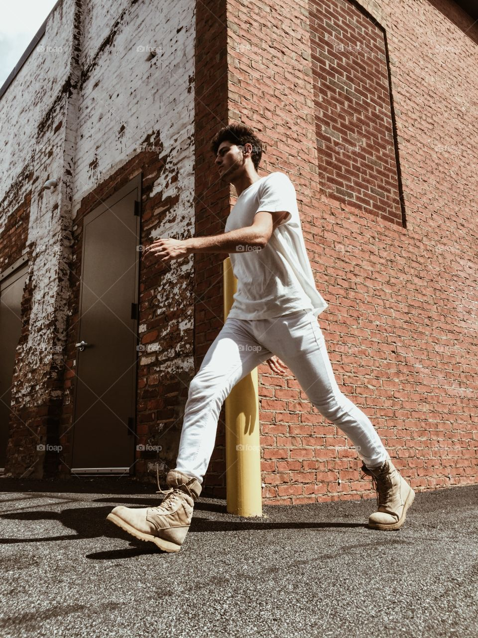 A young man walking down the street wearing white clothes.  Cool, urban city vibe.