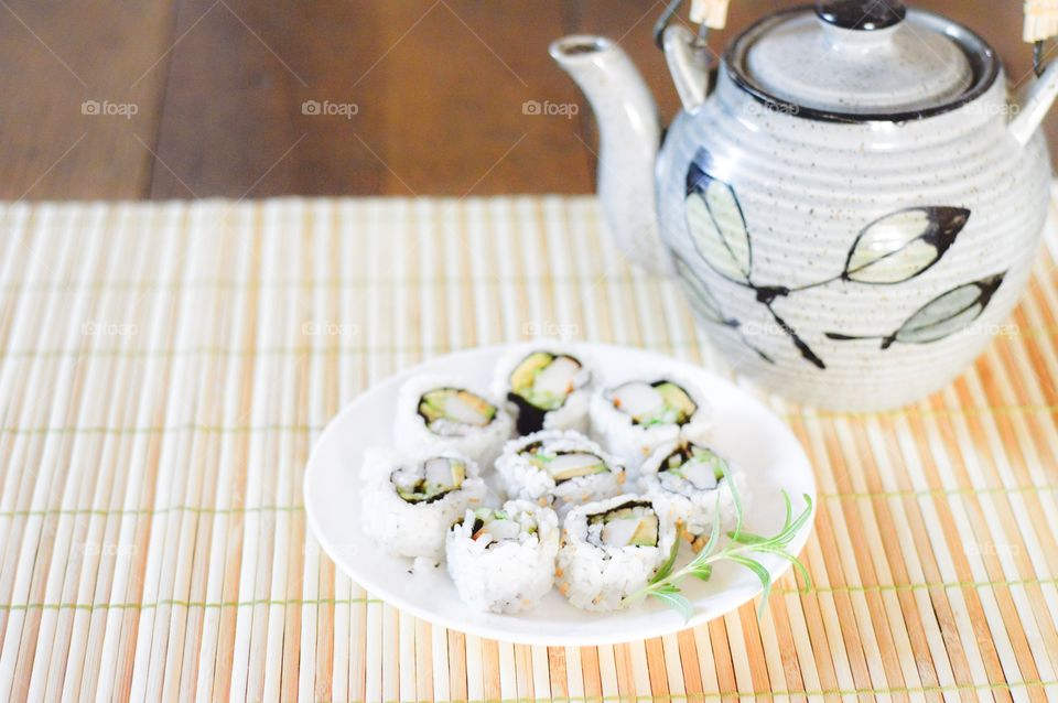 Sushi rolls and hot tea on bamboo mat