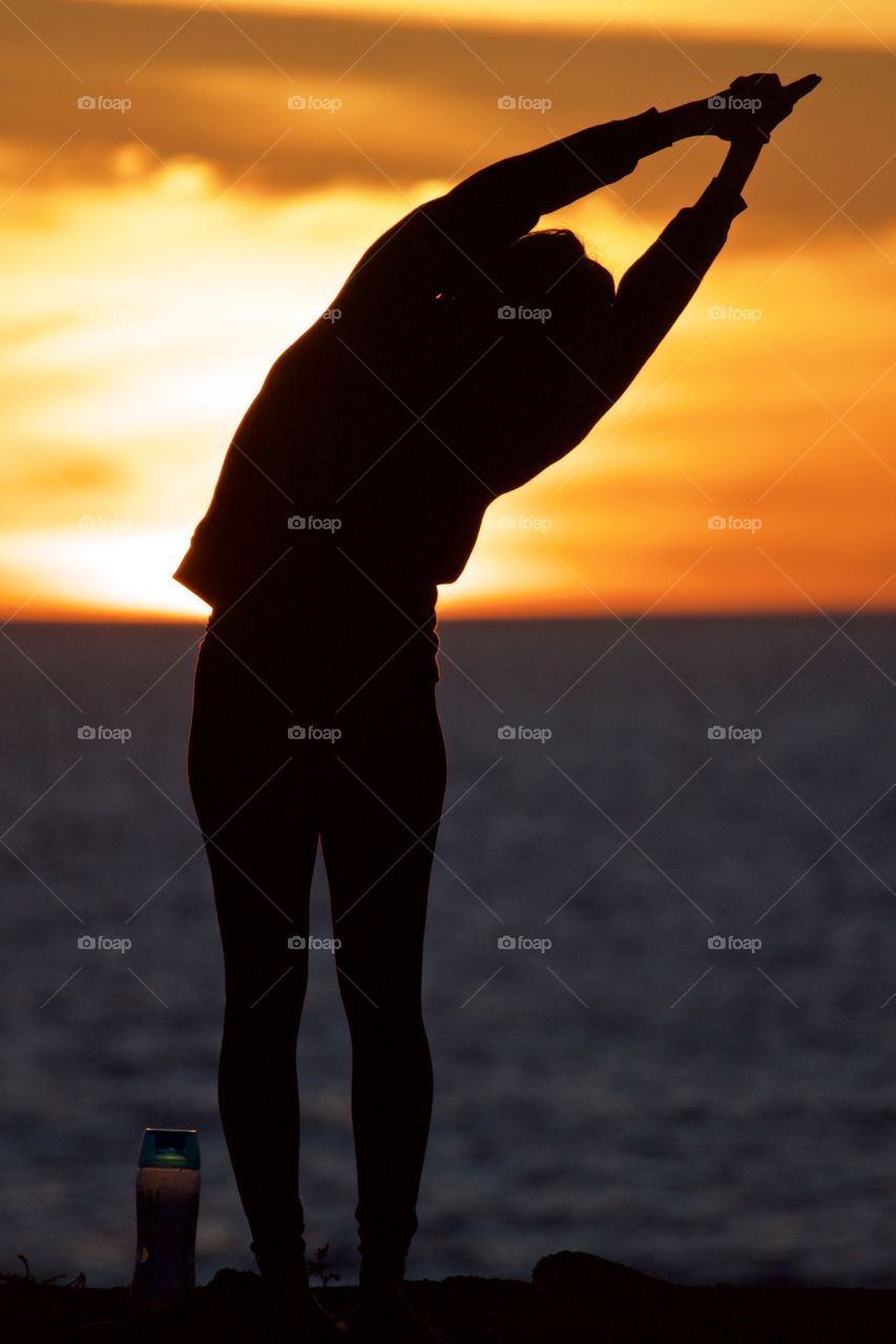 A woman doing yoga on a cliff at sunset