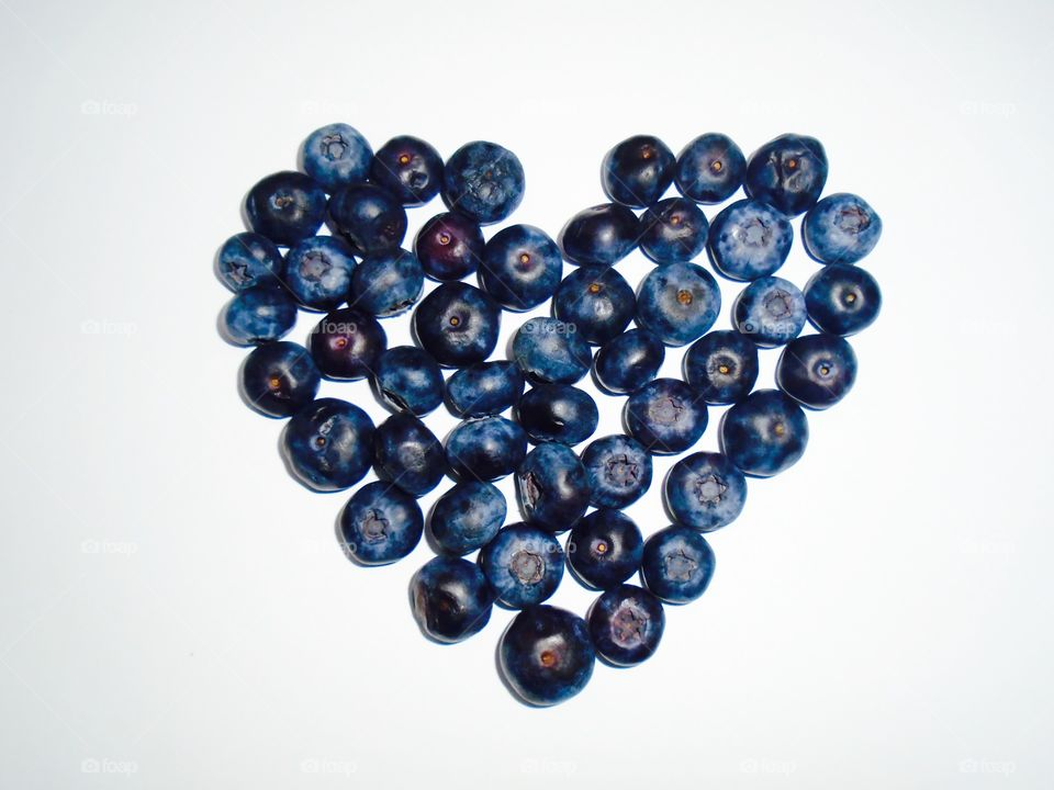 Heart shape made of blueberries on white background
